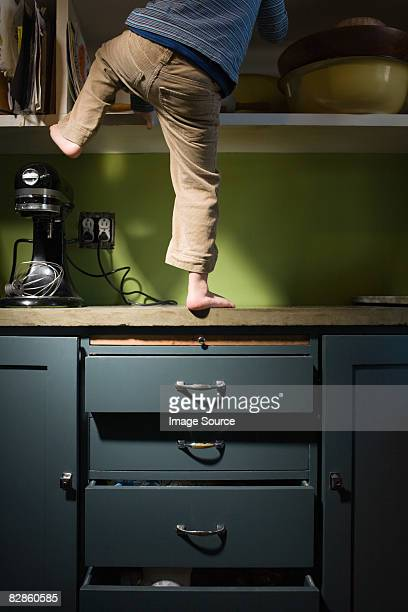 boy climbing in kitchen - hazard stock pictures, royalty-free photos & images