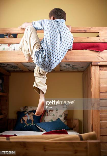 Boy Climbing into His Bunk Bed