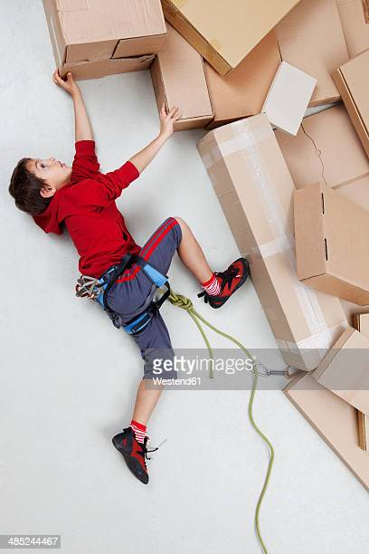 boy climbing mountains made of cardboard boxes