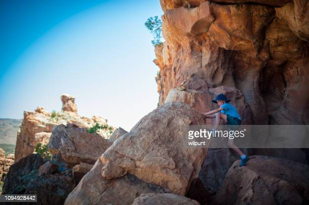 boy climbing on a rock in a cave - wilderness area stock pictures, royalty-free photos & images