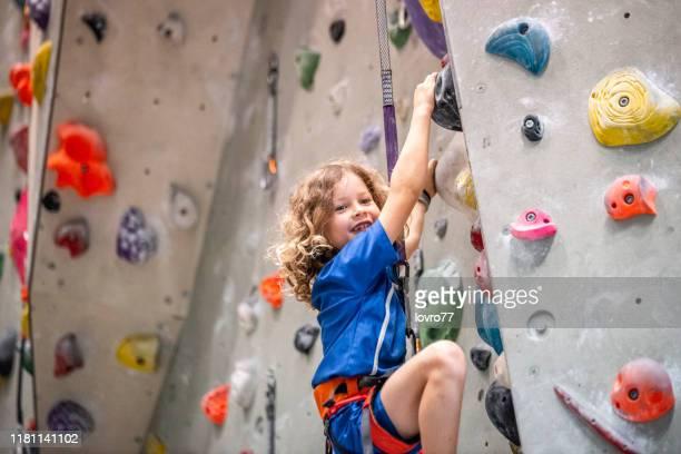クライミングウォールに登る少年 - クライミングウォール ストックフォトと画像
