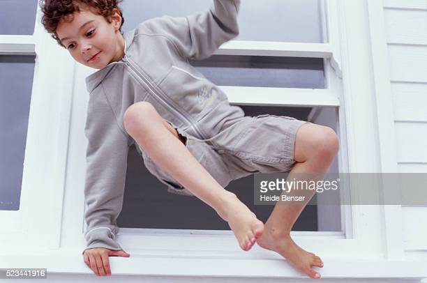 Boy Climbing out of Window