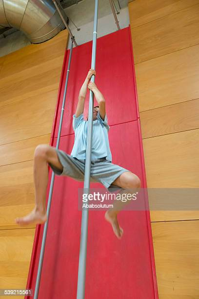Boy Climbing Pole Using his Arms Only in School Gymnasium