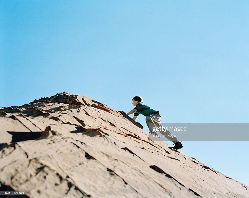 Boy (11-13) climbing rock in desert : Foto stock