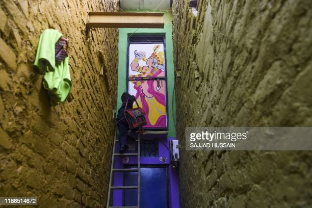 Boy climbs up a ladder to enter a home adorned with a mural painted by artists from 'Delhi Street Art' group at the Raghubir Nagar slum in New Delhi...
