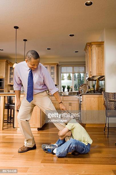 boy clinging to father - dragging stock pictures, royalty-free photos & images