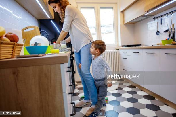 boy clinging to his mother leg - perching stock pictures, royalty-free photos & images