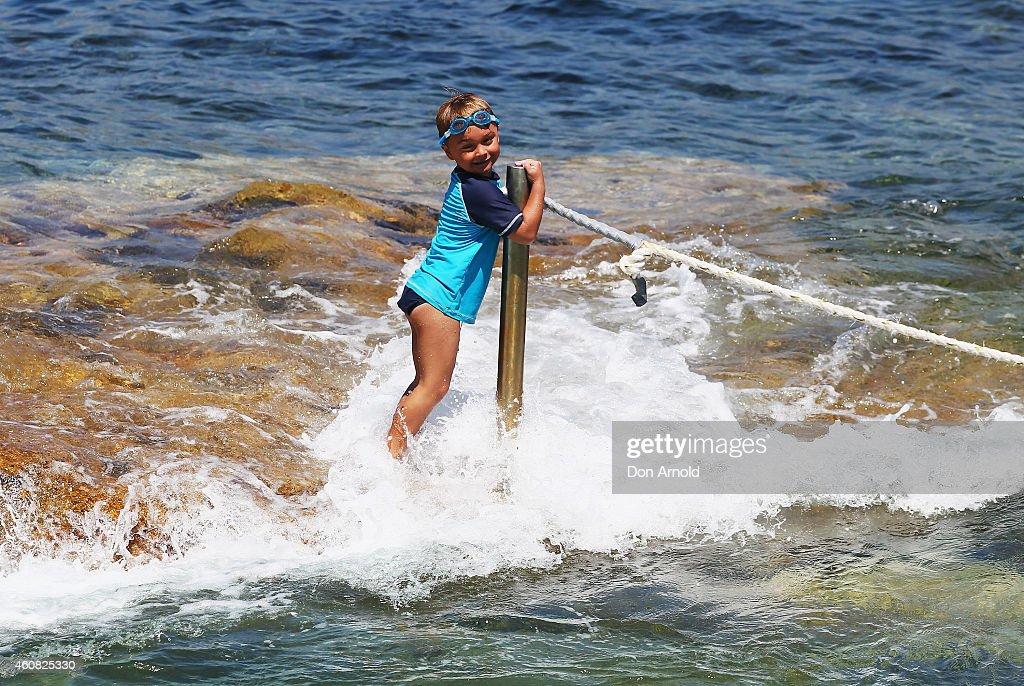 A boy clings onto a pole near the rock pools at North Bondi at Bondi Beach on December 25, 2014 in Sydney, Australia. Bondi Beach is a popular tourist destination on Christmas Day.