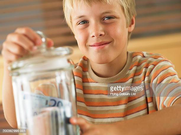 Boy (7-9) closing lid on jar of money, smiling, portrait, close-up