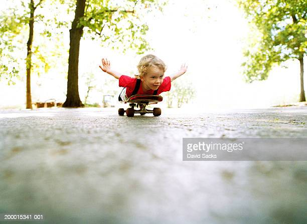 boy (2-4) coasting on skateboard, ground view - skating stock pictures, royalty-free photos & images