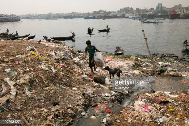 A boy collect usable goods from garbage in the Buriganga River in Dhaka Bangladesh on March 21 2020 The chemical waste of mills and factories...