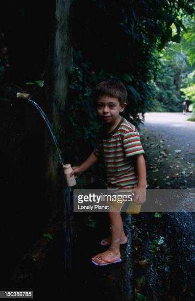Boy collecting water from fountain at Paineiras, Floresta da Tijuca.