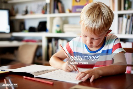 Boy coloring at table : Stock Photo