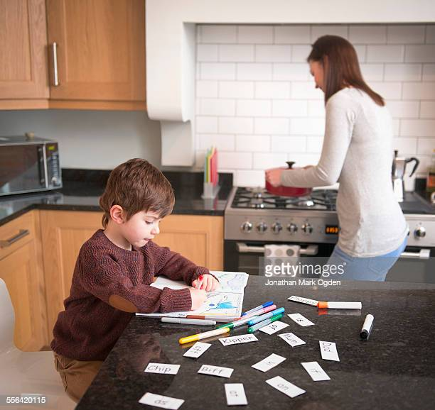Boy coloring in book on kitchen counter as mother prepares dinner