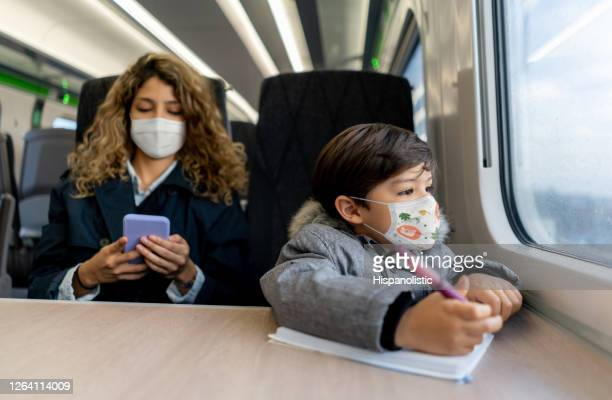 boy coloring while traveling by train with his mother wearing facemask - rail transportation stock pictures, royalty-free photos & images