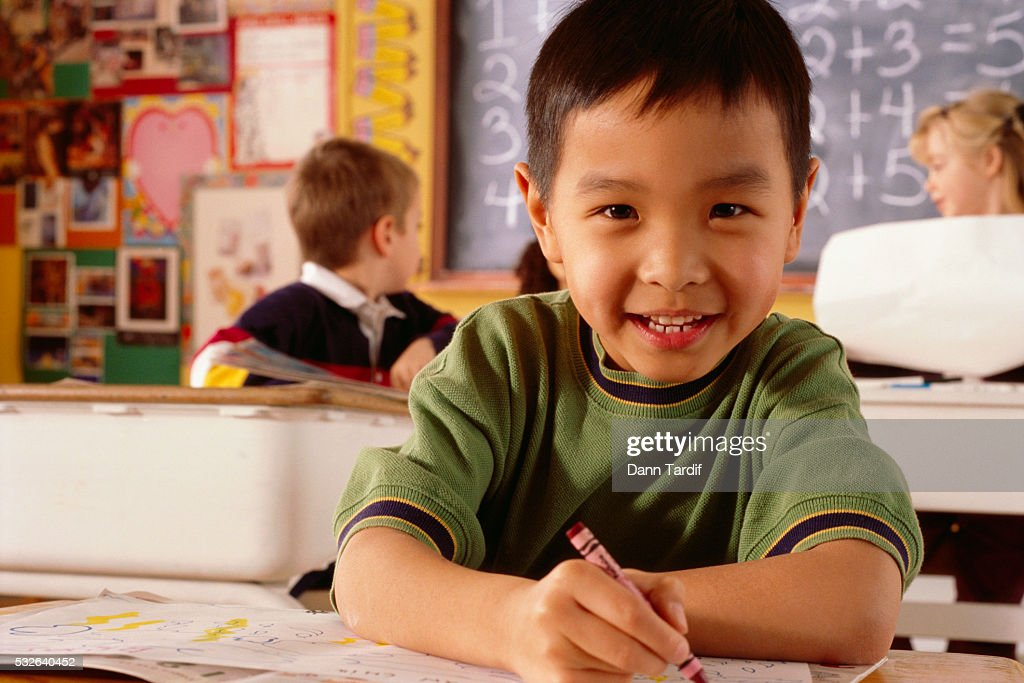 Boy Coloring With Crayons In Classroom Stock Photo