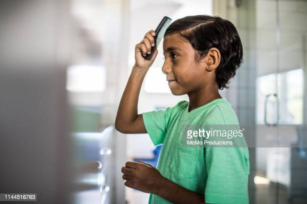 boy combing his hair in the mirror - penteando imagens e fotografias de stock