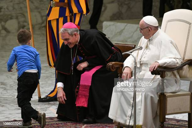 A boy coming from the audience onto the stage runs past Pope Francis and Prefect of the Papal Household Georg Ganswein during the weekly general...