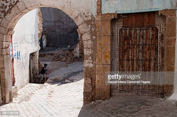 Boy coming out from his home in the medina