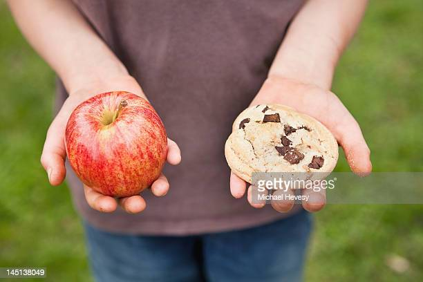 A Boy Comparing An Apple And A Cookie