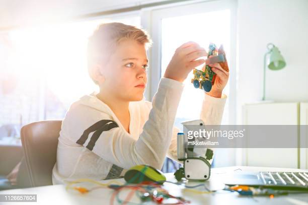 Boy concentrates on a science project and he creates a robot with a circuit board