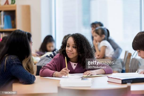 boy concentrates on work while girls gossip - aluna da escola secundária imagens e fotografias de stock