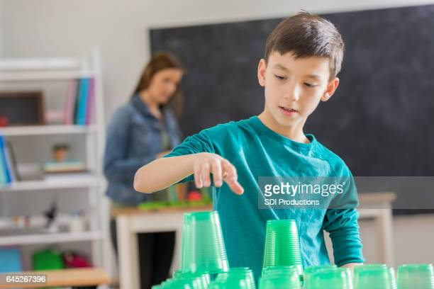 Boy concentrates while stacking cups