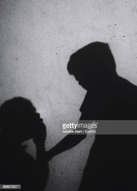 Boy Consoling Crying Sister Casting Shadow On Wall