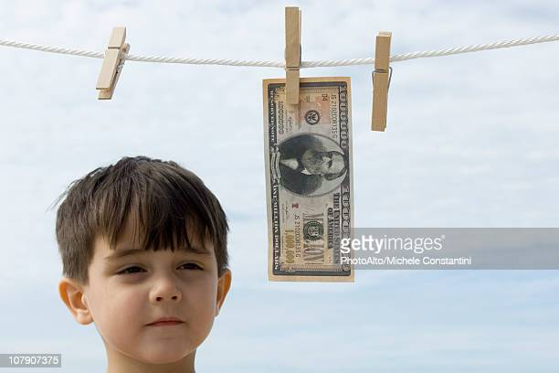 Boy contemplating one million dollar bill hanging on clothes-line