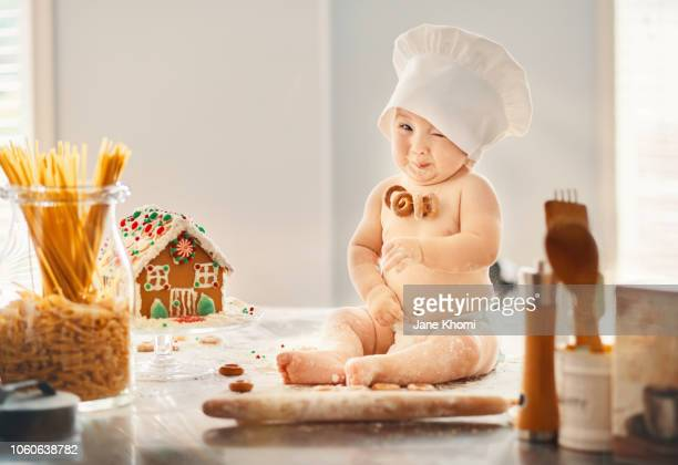 boy cooking a gingerbread house - コック帽 ストックフォトと画像
