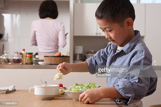 Boy Cooking Salad at Table