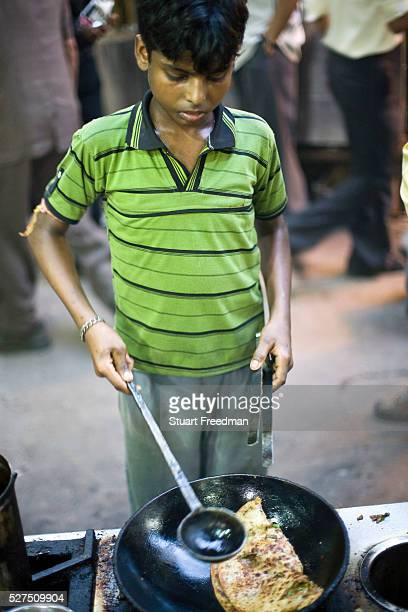 A boy cooks a paratha in a pan of oil at the famous Parawthe Wala restaurant in Old Delhi India The parantha is an Indian fried bread folded and...