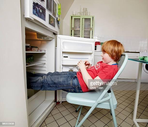 boy cooling feet in refrigirator