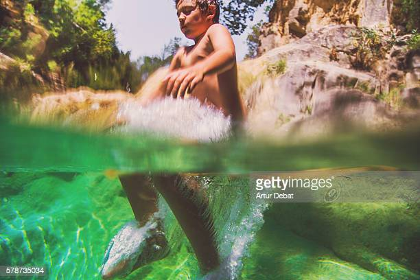 Boy cooling off on a beautiful green pool in the river, jumping with underwater view on summertime in the Catalan Pyrenees.