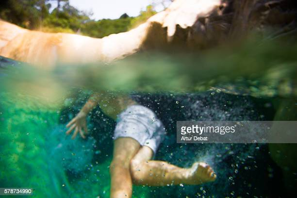 Boy cooling off on a beautiful green pool in the river, swimming with underwater view on summertime in the Catalan Pyrenees.