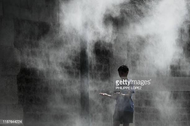 TOPSHOT A boy cools off under a public water spray on the bank of the Seine river in Paris on July 25 2019 as a new heatwave hits Europe After...