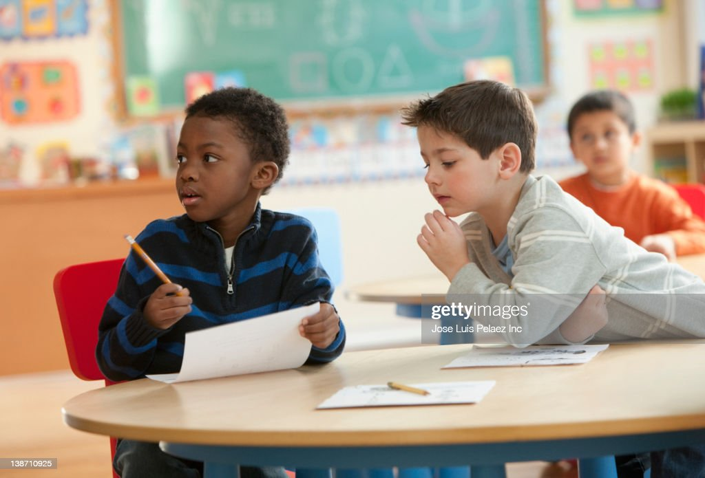 Boy copying off classmates paper : Stock Photo