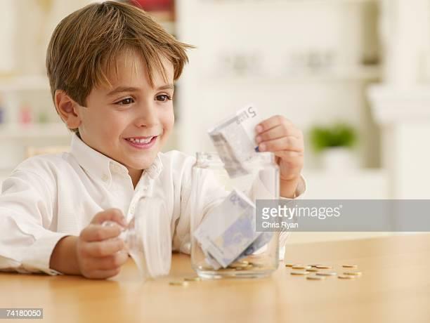 Junge Geld zählen in Glas jar