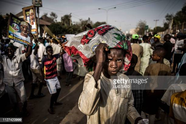 TOPSHOT A boy cover himself with a plastic bag while All Progressives Congress Party supporters celebrate initial results released by the Nigerian...