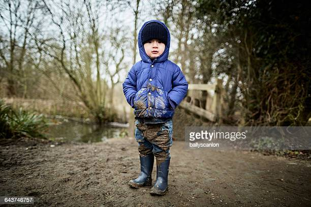 boy covered in mud in countryside. - wellington boot stock pictures, royalty-free photos & images