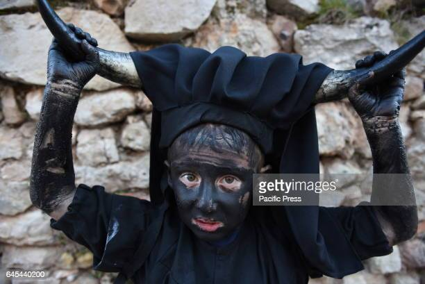 A boy covered in oil and soot carrying bull horns on his head and cowbells on a belt representing the devil pictured during a traditional carnival...
