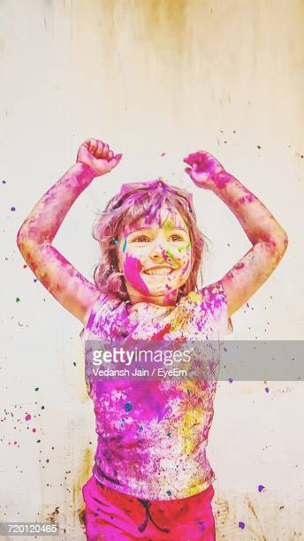 Boy Covered With Colored Powder Standing Against Wall