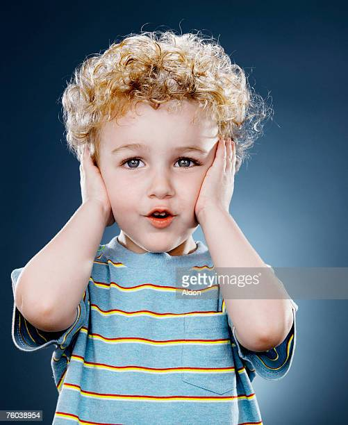 Boy (2-4) covering ears, close-up