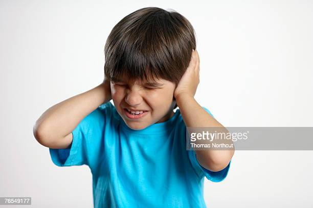 Boy (3-5) covering ears with hands, close-up