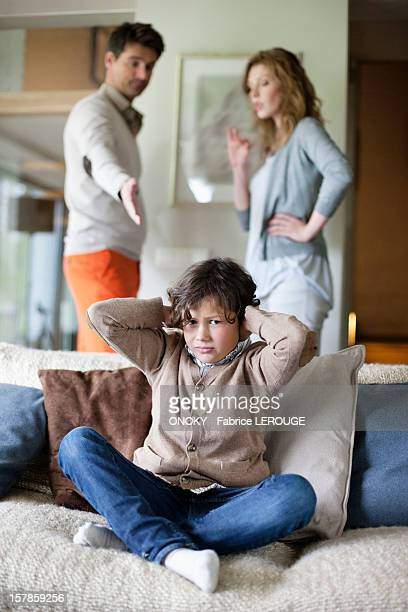 Boy covering ears with hands while his parents arguing in the background