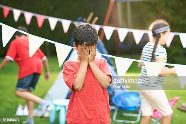 Boy covering his eyes for hide and seek with brother and sister in garden