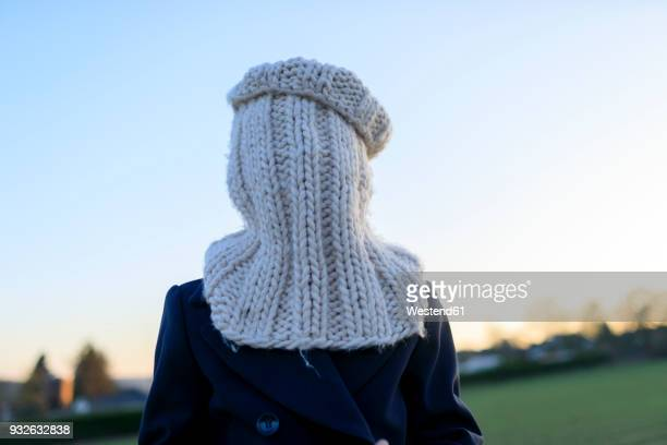 boy covering his face with knitted round scarf - froid humour photos et images de collection