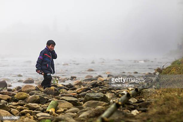 boy covering his mouth at riverbank - merten snijders stock pictures, royalty-free photos & images