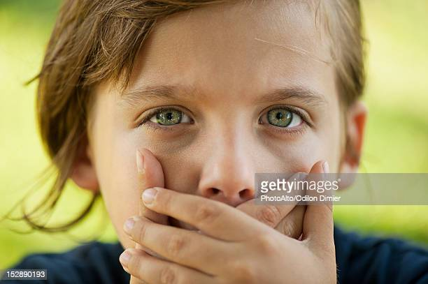 Boy covering mouth with hands