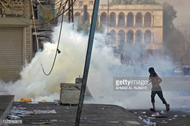 A boy covers his face with a rag as he flees from tear gas fumes as protesters clash with riot police amidst demonstrations against state corruption...